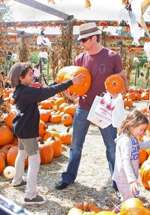 Hugh Jackman con su familia escogiendo calabazas